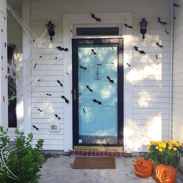 Halloween door decorated with 3D bats and spiderwebs - Charleston Crafted