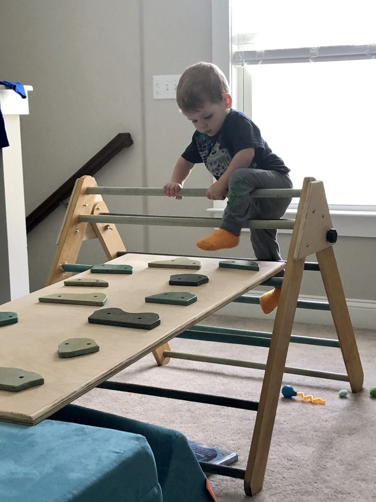 toddler climbing a homemade pikler triangle