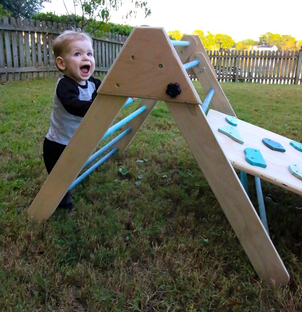 Kid climbing Pikler Triangle