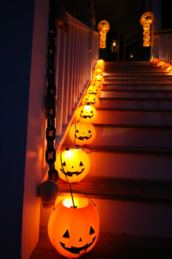 pumpkin pails with twinkle lights on stairs halloween