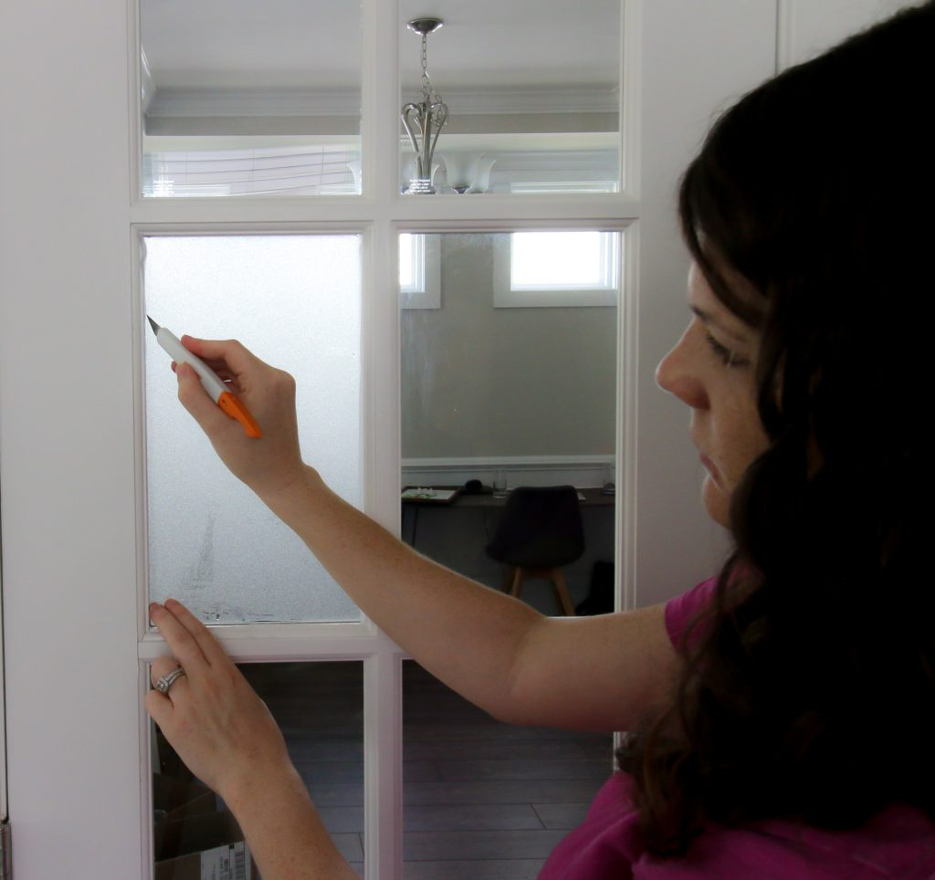 using exacto knife to trim frosted glass privacy film on a french door glass
