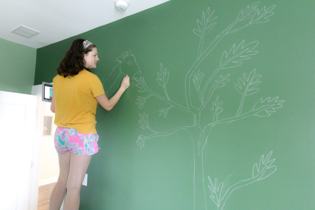sketching a mural on the wall with chalk