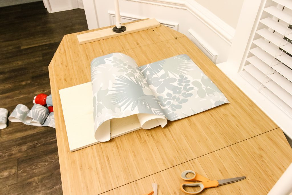 Applying wallpaper to shelf sides
