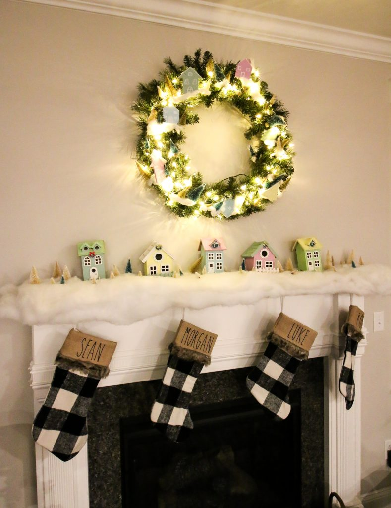 pastel wooden houses on a mantel with buffalo check stockings