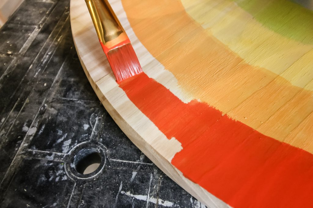 painting tabletop with a rainbow pattern