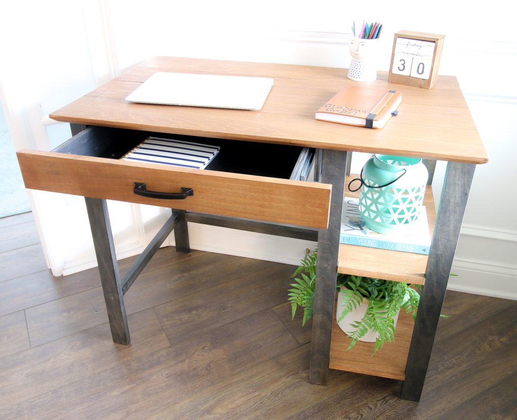 Drawer open on writing desk with supplies