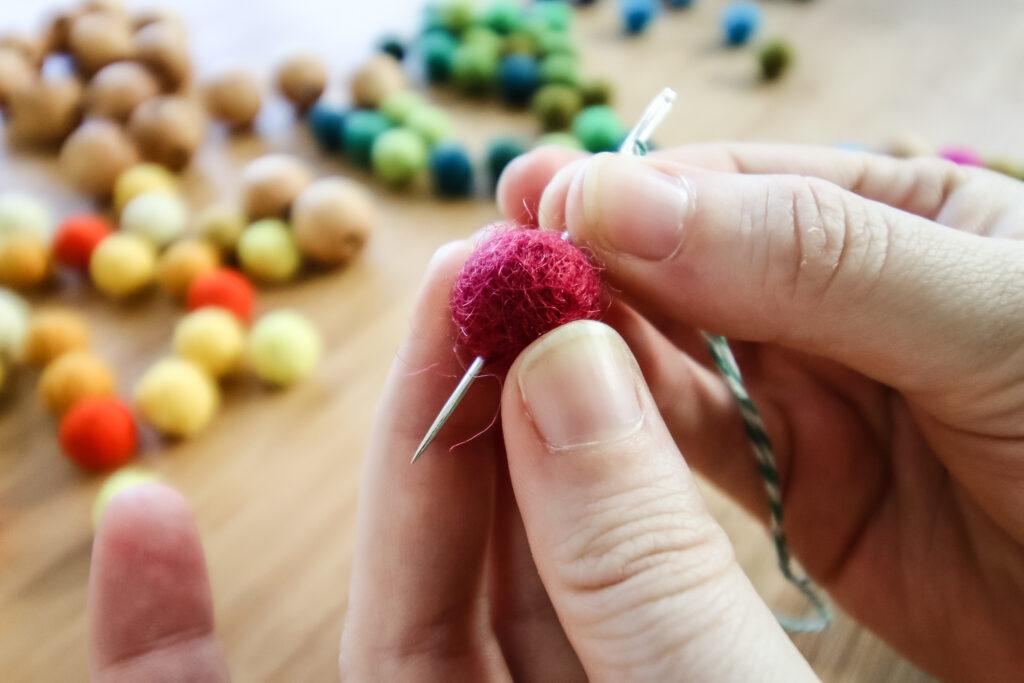 thread needle through felt ball pom pom