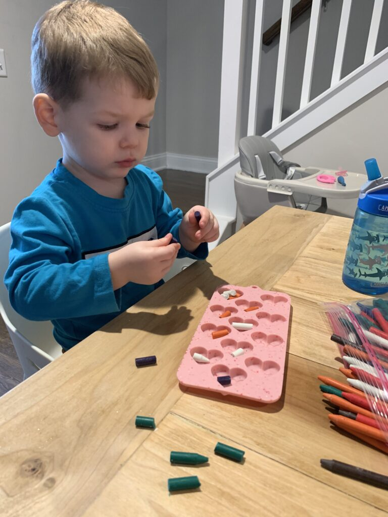 toddler breaking up crayons to melt into shapes