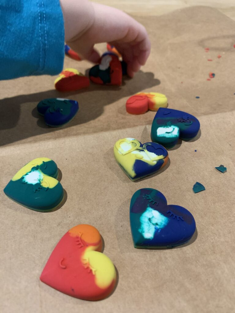 toddler hands coloring with heart shaped crayons