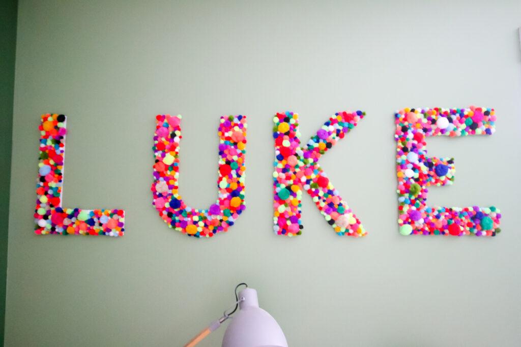 DIY pom pom letters spelling LUKE