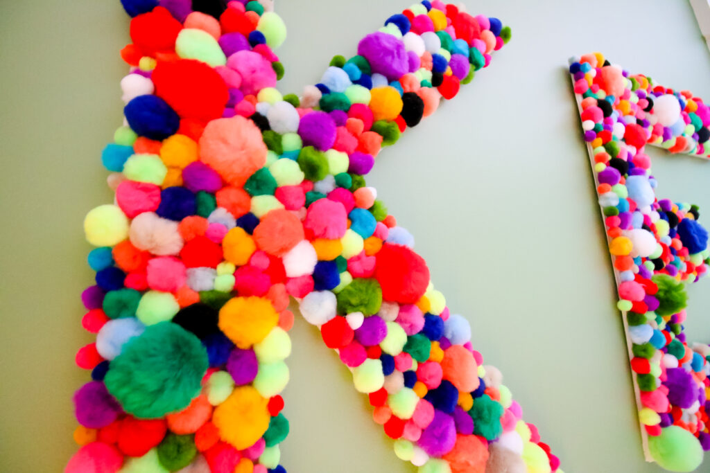 Close up of DIY wall hanging pom pom letters