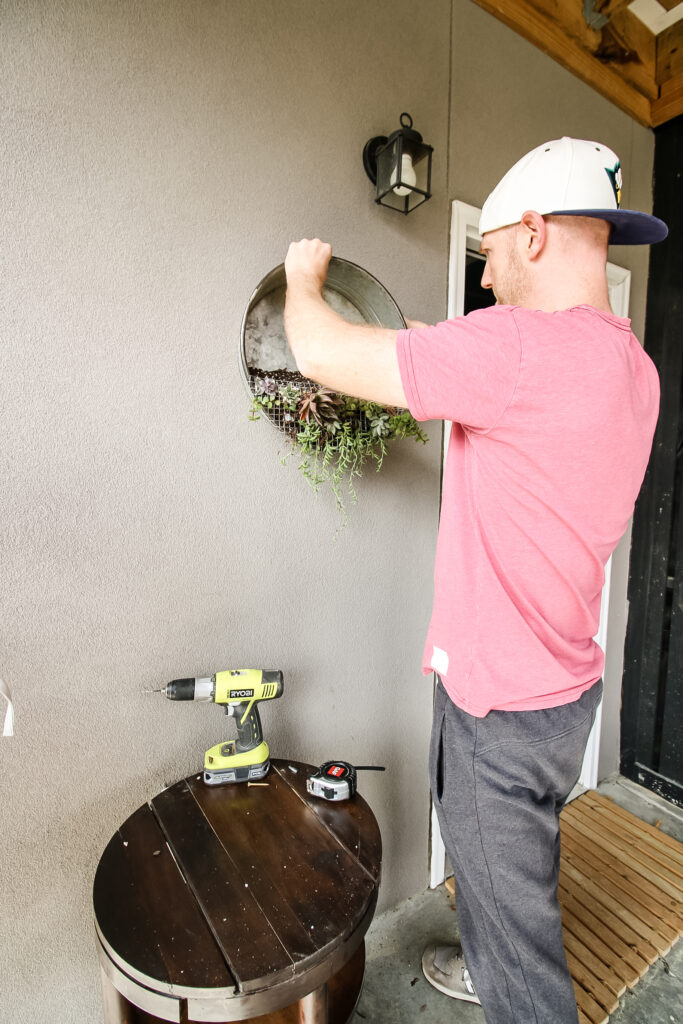 hanging a galvanized metal wall planter on a patio wall using 2 screws and d hooks
