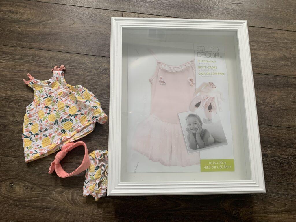 DIY baby clothes shadow box display