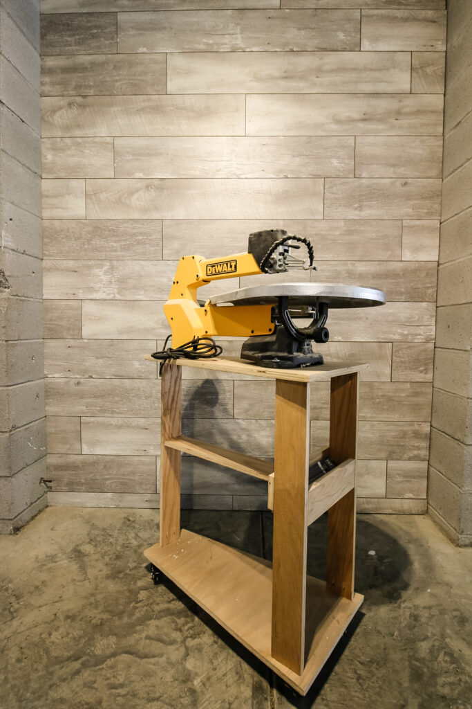 Photo of scroll saw stand in front of feature wall
