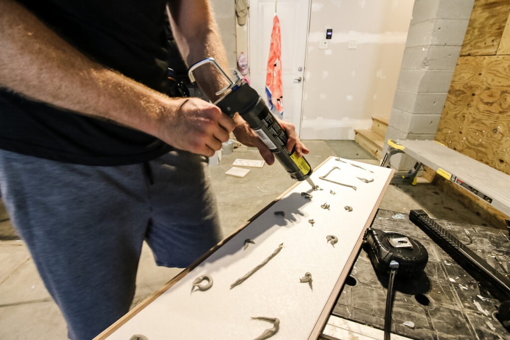 Apply adhesive caulk to back of flooring