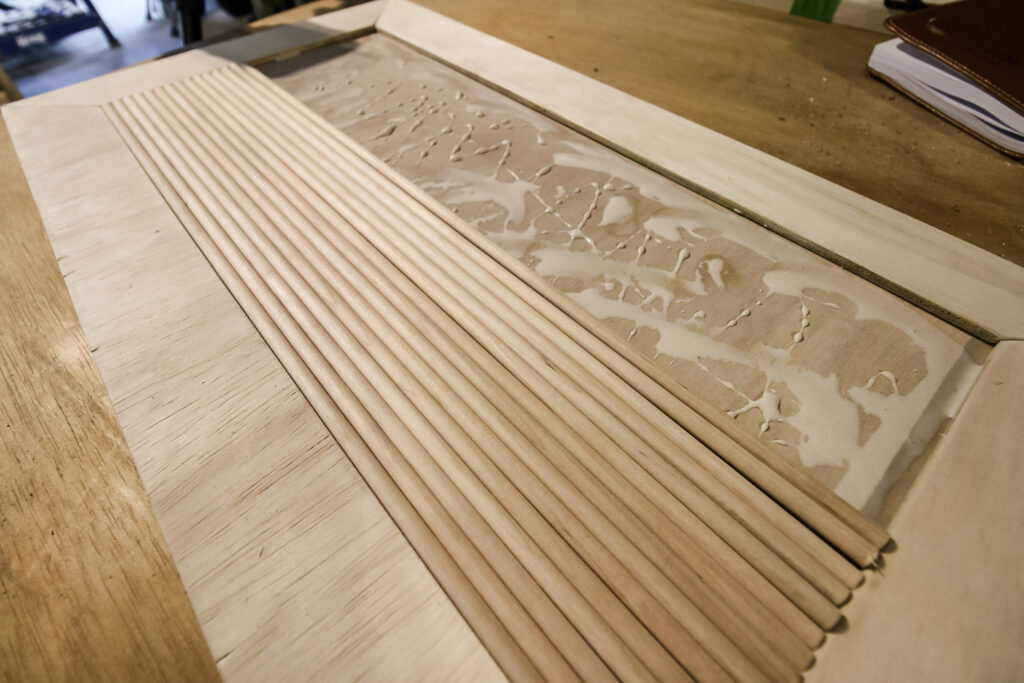 Laying wood dowels to make fluted door