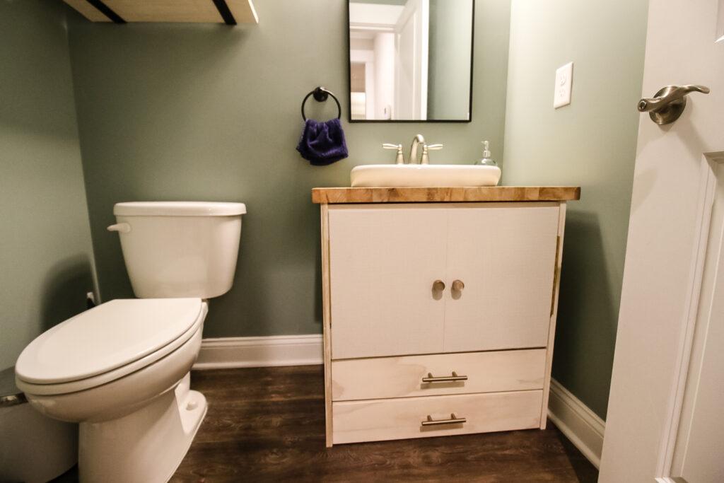 Wide shot of pedestal sink vanity in half bathroom
