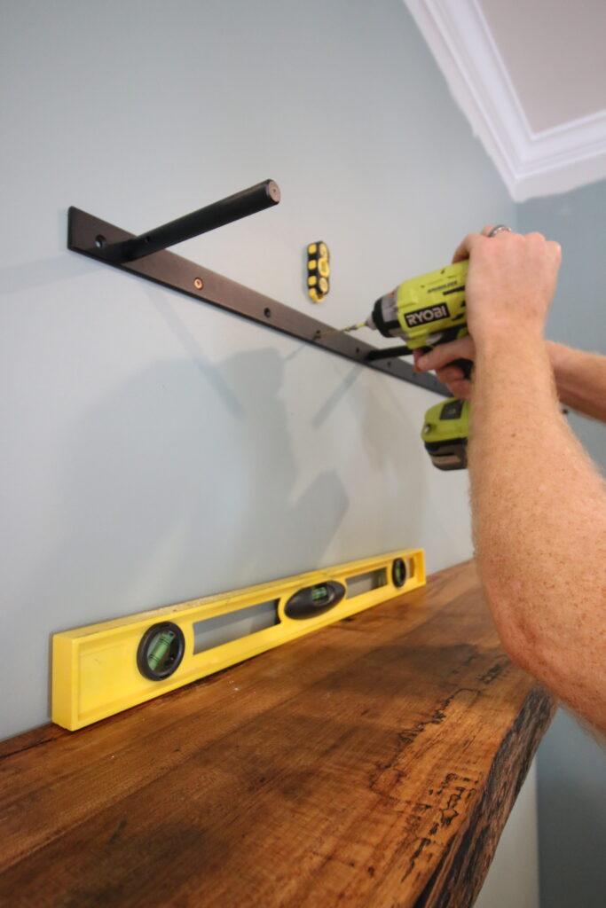 Attaching floating shelf bracket to wall